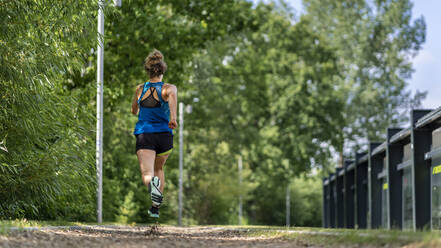 Young woman jogging on a woodchip trail - STSF02183