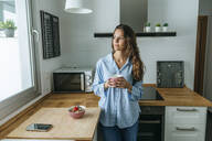 Young woman wearing pyjama in kitchen at home looking out of window - KIJF02533