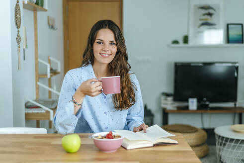 Portrait of smiling young woman having breakfast at home - KIJF02536