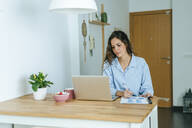 Young woman using laptop during breakfast at home - KIJF02539