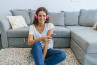 Portrait of smiling young woman sitting on floor in living room listening to music with cell phone - KIJF02545