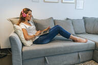 Relaxed young woman on couch at home with headphones and laptop - KIJF02548