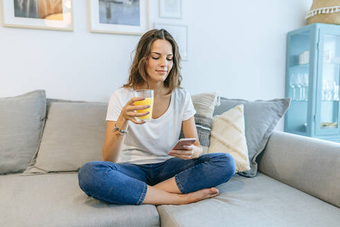 Young woman sitting on sofa with juice using cell phone - KIJF02554