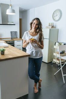 Portrait of smiling young woman drinking orange juice in the kitchen - KIJF02557