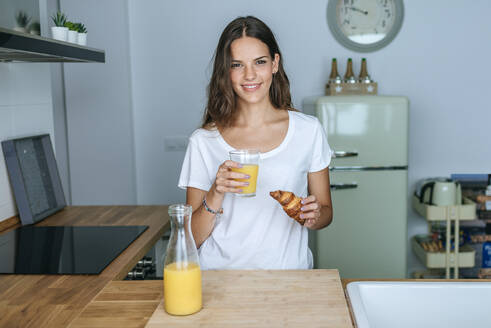 Portrait of smiling young woman having breakfast with juice and croissant in the kitchen - KIJF02560