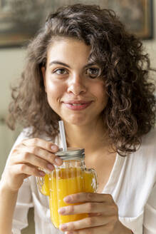 Portrait of smiling young woman with glass of orange juice - AFVF03726