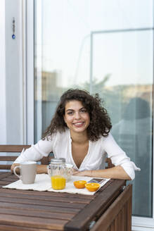 Portrait of smiling young woman with orange juice on balcony - AFVF03753