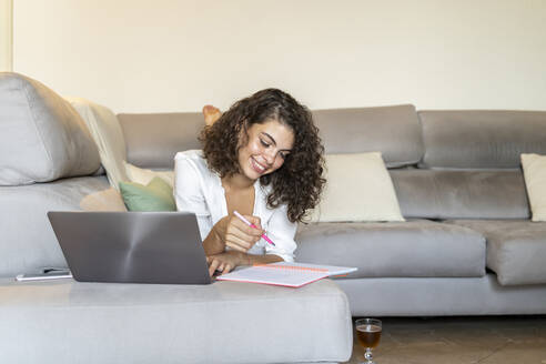 Smiling young woman taking notes and using laptop on couch at home - AFVF03759