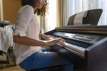 Woman playing piano at home - AFVF03777