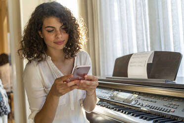 Young woman using cell phone at the piano at home - AFVF03780