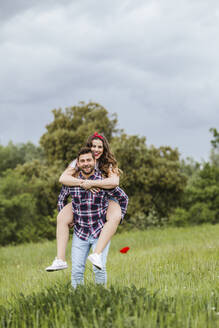Young man carrying girlfriend piggyback in nature - LJF00627