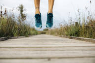 Feet of female jogger, jumping on a wooden walkway - JRFF03648