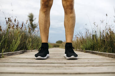 Black running shoes, male jogger standing on a wooden walkway - JRFF03654