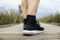 Rear view of black running shoes, male jogger standing on a wooden walkway - JRFF03657