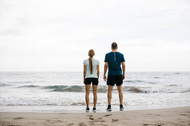Young couple standing side by side on the beach - JRFF03675