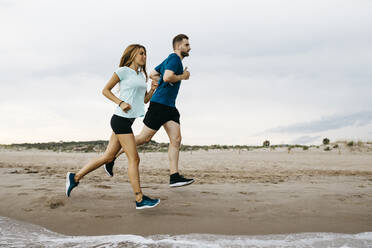 Young couple jogging on the beach - JRFF03678