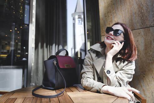 Businesswoman sitting outdoors, making phone calls - EYAF00371