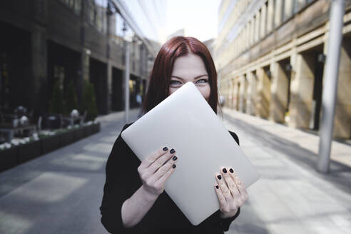 Businesswoman covering face with laptop - EYAF00377