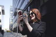 Stylish woman taking selfies in the city - EYAF00383