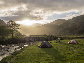 Tents on grassy land against cloudy sky during sunset, Scotland, UK - HUSF00058