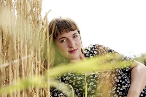 Deutschland,NRW,Ruhrgebiet,Stadt Essen,junge Frau mit Blumenkleid in einem Getreidefeld - FLLF00266