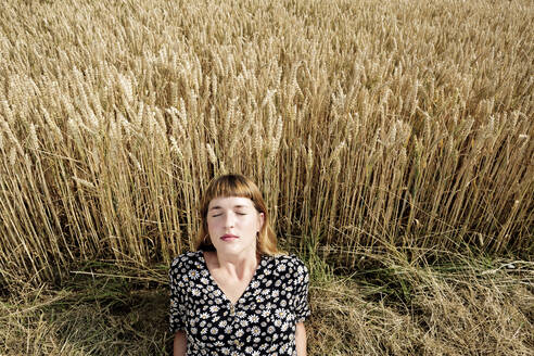 Portrait of young woman with eyes closed relaxing in front of grain field - FLLF00269