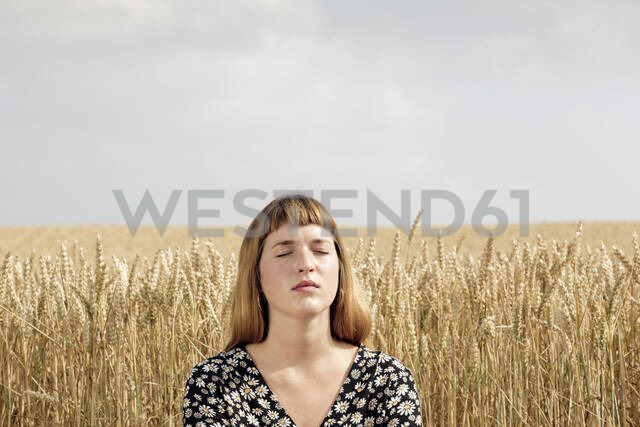 Portrait of young woman with eyes closed relaxing in front of grain field - FLLF00272 - FL/Westend61