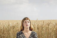 Portrait of young woman with eyes closed relaxing in front of grain field - FLLF00272
