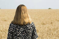 Back view of woman standing in front of grain field - FLLF00275