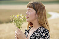 Young woman with eyes closed smelling bunch of chamomile flower - FLLF00278