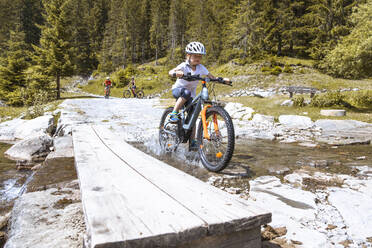 Girl crossing a mountain stream with her e-mountain bike - FKF03539