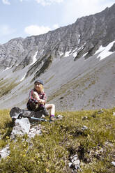 Girl having a break during a hike in the mountains - FKF03542