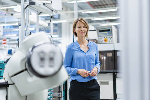 Portrait of businesswoman at assembly robot in a factory - DIGF07811