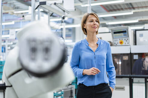 Portrait of businesswoman at assembly robot in a factory - DIGF07814