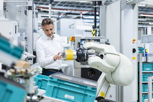 Businessman examining assembly robot in a factory - DIGF07817