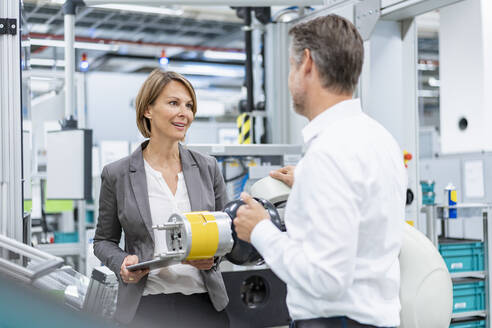 Businesswoman and man talking at assembly robot in a factory - DIGF07823
