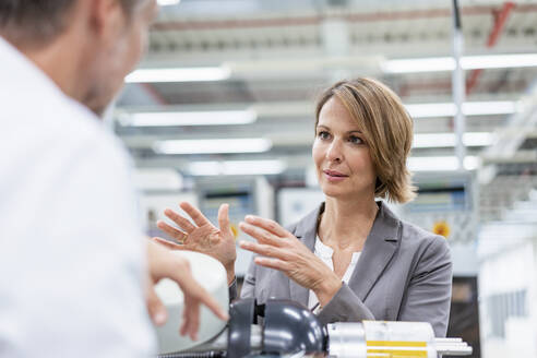 Businesswoman and man talking at assembly robot in a factory - DIGF07829