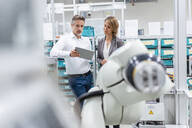 Businesswoman and man with tablet talking at assembly robot in a factory - DIGF07832
