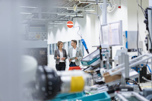Businesswoman and businessman with tablet walking and talking in a modern factory - DIGF07835