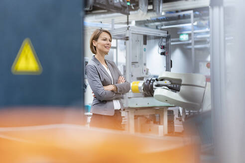 Portrait of a confident businesswoman in a modern factory - DIGF07838