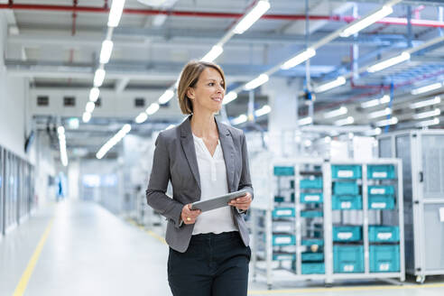 Smiling businesswoman with tablet in a modern factory - DIGF07853