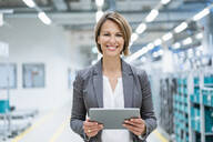 Portrait of smiling businesswoman with tablet in a modern factory - DIGF07868