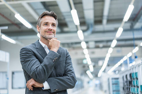 Portrait of a confident businessman in a modern factory - DIGF07877