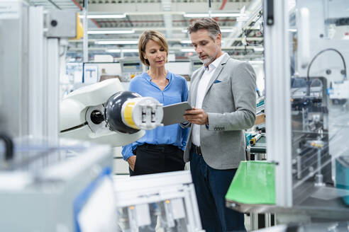 Businessman with tablet and woman talking at assembly robot in a factory - DIGF07880