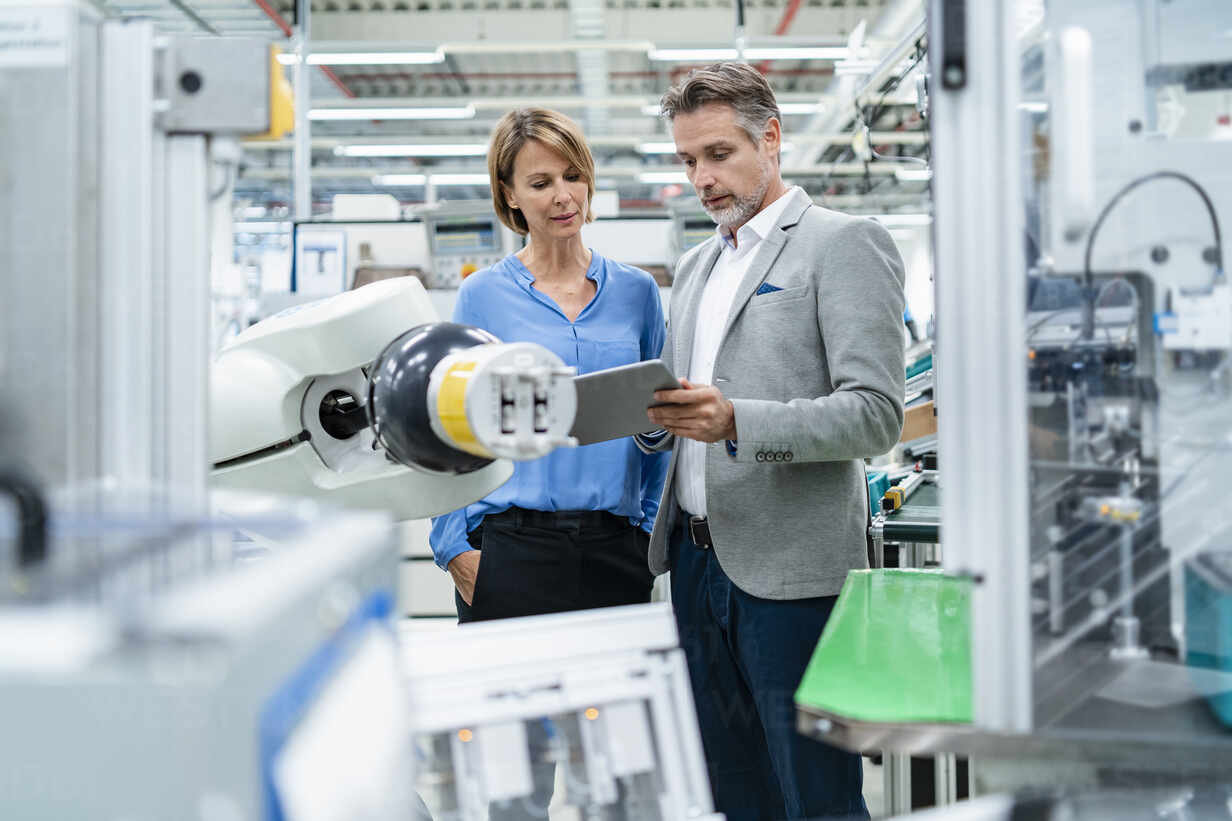 Businessman with tablet and woman talking at assembly robot in a factory - DIGF07880 - Daniel Ingold/Westend61