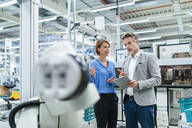 Businessman with tablet and woman talking at assembly robot in a factory - DIGF07883