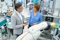 Businessman with tablet and woman talking at assembly robot in a factory - DIGF07886