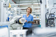 Businesswoman with tablet at assembly robot in a factory - DIGF07889