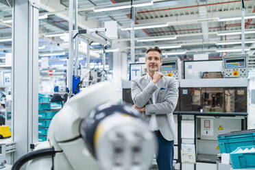 Portrait of confident businessman at assembly robot in a factory - DIGF07892