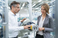 Businesswoman and man talking at assembly robot in a factory - DIGF07895